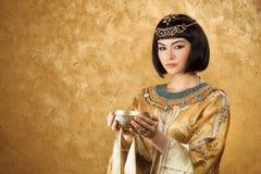 Όμορφη γυναίκα όπως την αιγυπτιακή βασίλισσα Κλεοπάτρα με το φλυτζάνι στο χρυσό υπόβαθρο Στοκ Φωτογραφίες