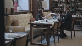 Όμορφη γυναίκα brunette και ξανθή γενειοφόρος συνεδρίαση ανδρών στον πίνακα στην εργασία καφέδων Το lap-top, τα έγγραφα και τα γυ απόθεμα βίντεο