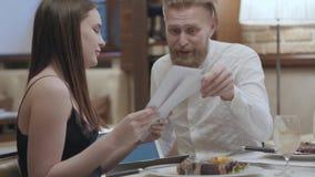 Όμορφη γυναίκα brunette και ξανθή γενειοφόρος συνεδρίαση ανδρών στον πίνακα στον καφέ που συζητά τα έγγραφα Η εκμετάλλευση ατόμων απόθεμα βίντεο
