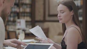 Όμορφη γυναίκα brunette και ξανθός γενειοφόρος άνδρας που εργάζονται στον πίνακα στον καφέ κοντά επάνω Η κυρία διαβάζει τα έγγραφ απόθεμα βίντεο