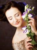 Όμορφη γυναίκα brunette με τα ιώδη λουλούδια Στοκ Φωτογραφία