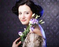 Όμορφη γυναίκα brunette με τα ιώδη λουλούδια Στοκ Εικόνες