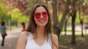 Όμορφη γυναίκα brunette με τα ρόδινα χείλια που φυσούν το φιλί απόθεμα βίντεο