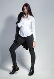 Όμορφη γυναίκα brunette με την καλή μακρυμάλλη τοποθέτηση σε ένα άσπρο πουκάμισο και τα τζιν σε ένα στούντιο η μόδα σεντονιών βάζ Στοκ εικόνες με δικαίωμα ελεύθερης χρήσης