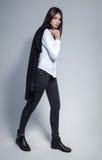 Όμορφη γυναίκα brunette με την καλή μακρυμάλλη τοποθέτηση σε ένα άσπρο πουκάμισο και τα τζιν σε ένα στούντιο η μόδα σεντονιών βάζ Στοκ Φωτογραφίες