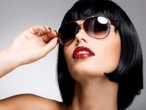 Όμορφη γυναίκα brunette με τον πυροβολισμό hairstyle με τα κόκκινα γυαλιά ηλίου Στοκ Φωτογραφία