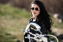 Όμορφη γυναίκα brunette μοτοσικλετών με μια κλασική μοτοσικλέτα γ στοκ εικόνα