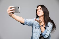 Όμορφη γυναίκα brunette που κάνει ένα selfie που φυσά ένα φιλί που κρατά το smartphone απομονωμένο σε ένα γκρίζο υπόβαθρο στοκ εικόνες