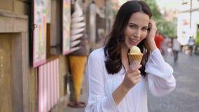 Όμορφη γυναίκα brunette που τρώει το εύγευστο και γλυκό παγωτό απόθεμα βίντεο