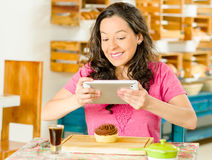 Όμορφη γυναίκα brunette που φορά τη ρόδινη συνεδρίαση πουκάμισων από τον πίνακα μέσα στο αρτοποιείο, που χρησιμοποιεί το κινητό τ Στοκ Φωτογραφίες