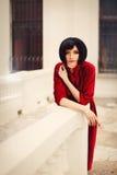 Όμορφη γυναίκα brunette που φορά το κόκκινο φόρεμα, που θέτει σε ένα κάστρο Στοκ Φωτογραφίες
