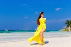 Όμορφη γυναίκα brunette σε ένα κίτρινο φόρεμα στην τροπική θάλασσα γ στοκ φωτογραφίες