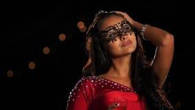 Όμορφη γυναίκα brunette σε μια μάσκα καρναβαλιού επάνω φιλμ μικρού μήκους