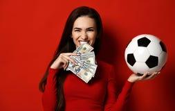 Όμορφη γυναίκα brunette στη σφιχτά κόκκινη σφαίρα ποδοσφαίρου λαβής φορεμάτων σε ένα χέρι και τα δαγκώματα ένα wad των δολαρίων στοκ φωτογραφία