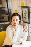 Όμορφη γυναίκα brunette στο άσπρο πουλόβερ σε έναν καφέ κατανάλωσης καφέδων Άσπρο και κίτρινο εσωτερικό Hipster του καφέ στοκ φωτογραφίες με δικαίωμα ελεύθερης χρήσης