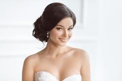 Όμορφη γυναίκα brunette ως νύφη με τη ρόδινη γαμήλια ανθοδέσμη στο λευκό στοκ φωτογραφίες με δικαίωμα ελεύθερης χρήσης