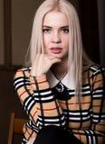 Όμορφη γυναίκα glamor blondie στο κομψό σακάκι με το βράδυ makeup, τη συνεδρίαση και την τοποθέτηση Στοκ Εικόνες