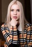 Όμορφη γυναίκα glamor blondie στο κομψό σακάκι με το βράδυ makeup, τη συνεδρίαση και την τοποθέτηση Στοκ Φωτογραφία
