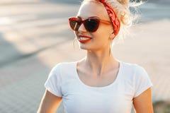 Όμορφη γυναίκα hipster με τα κόκκινα χείλια και τα γυαλιά ηλίου στο stre Στοκ Φωτογραφίες