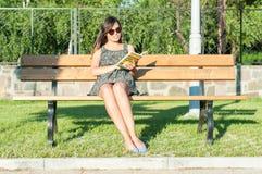 Όμορφη γυναικεία συνεδρίαση στον πάγκο και ανάγνωση Στοκ Φωτογραφία