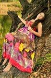 Όμορφη γυναικεία συνεδρίαση στο δέντρο Στοκ Φωτογραφίες