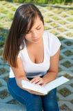 Όμορφη γυναικεία συνεδρίαση στο πάρκο και το σημειωματάριο ανάγνωσης Στοκ Φωτογραφίες