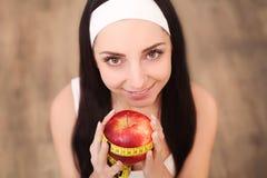 Όμορφη εκμετάλλευση γυναικών και μέτρηση του μήλου με τη μέτρηση της ταινίας Στοκ Φωτογραφία