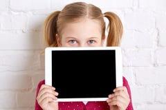 Όμορφη εκμετάλλευση μικρών κοριτσιών και κρύψιμο πίσω από το lap-top διάστημα αντιγράφων Στοκ φωτογραφία με δικαίωμα ελεύθερης χρήσης