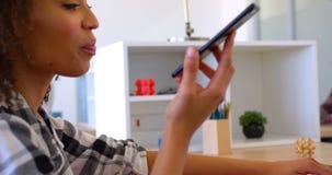 Όμορφη εκτός λειτουργίας θηλυκή εκτελεστική ομιλία αφροαμερικάνων στο κινητό τηλέφωνο χρησιμοποιώντας το lap-top στον τρόπο απόθεμα βίντεο