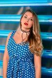 Όμορφη ελκυστική αρκετά μακρυμάλλης νέα γυναίκα στο μπλε φόρεμα Πόλκα-σημείων και στις γυναικείες κάλτσες και τα κόκκινα παπούτσι Στοκ φωτογραφίες με δικαίωμα ελεύθερης χρήσης