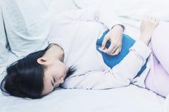 Όμορφη ελκυστική ασιατική γυναίκα που φορά την άσπρη συνεδρίαση πουκάμισων στο κρεβάτι στοκ εικόνες με δικαίωμα ελεύθερης χρήσης