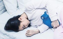 Όμορφη ελκυστική ασιατική γυναίκα που φορά την άσπρη συνεδρίαση πουκάμισων στο κρεβάτι στοκ εικόνες