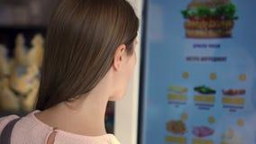 Όμορφη ελκυστική γυναίκα στη λεωφόρο Διαταγή των τροφίμων μέσω της μηχανής αυτοεξυπηρετήσεων στο εστιατόριο αλυσίδων γρήγορου γεύ φιλμ μικρού μήκους