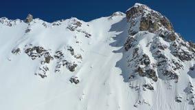 Όμορφη εναέρια άποψη ένα ογκώδες βουνό που καλύπτεται σχετικά με στο χιόνι σκονών με ένα άτομο που αναρριχείται σε το, 4k απόθεμα βίντεο