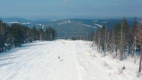 Όμορφη εναέρια άποψη των ανθρώπων σε μια κλίση σκι που αρχίζει να κάνει σκι κάτω μιας διαδρομής κοντά στα κωνοφόρα δέντρα και το  φιλμ μικρού μήκους