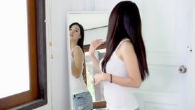 Όμορφη εξέταση επιδέσμου χαμόγελου γυναικών πορτρέτου ασιατική νέα στον καθρέφτη την κρεβατοκάμαρα απόθεμα βίντεο
