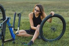 όμορφη επισκευή βουνών ποδηλάτων που επισκευάζει τη χαμογελώντας γυναίκα Νέο κορίτσι που επισκευάζει το ποδήλατο βουνών στοκ εικόνα