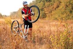 όμορφη επισκευή βουνών ποδηλάτων που επισκευάζει τη χαμογελώντας γυναίκα Νεαρός άνδρας που επισκευάζει το ποδήλατο βουνών Στοκ φωτογραφία με δικαίωμα ελεύθερης χρήσης