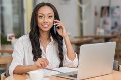 Όμορφη επιχειρηματίας αφροαμερικάνων που μιλά στο smartphone καθμένος κοντά στο lap-top στον καφέ Στοκ Εικόνες