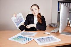 Όμορφη επιχειρηματίας με την οικονομική έκθεση στο γραφείο στοκ εικόνες