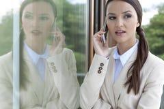 Όμορφη επιχειρηματίας που απαντά στο τηλέφωνο κυττάρων από την πόρτα γυαλιού Στοκ Εικόνα