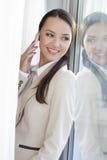 Όμορφη επιχειρηματίας που απαντά στο τηλέφωνο κυττάρων από το παράθυρο στην αρχή Στοκ Εικόνα