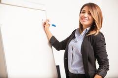 Όμορφη επιχειρηματίας που γράφει σε έναν πίνακα Στοκ Εικόνες