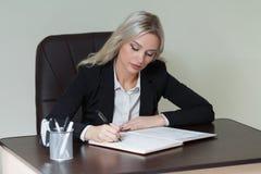Όμορφη επιχειρηματίας που γράφει σε ένα σημειωματάριο στην αρχή στοκ φωτογραφία με δικαίωμα ελεύθερης χρήσης