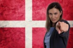 Όμορφη επιχειρηματίας που δείχνει το δάχτυλό της σε σας δανική σημαία β Στοκ Φωτογραφία