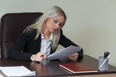 Όμορφη επιχειρηματίας που εργάζεται στο γραφείο γραφείων της με τα έγγραφα στοκ εικόνες