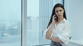 Όμορφη επιχειρηματίας που μιλά στο τηλέφωνο σε ένα γραφείο γυαλιού απόθεμα βίντεο