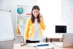 Όμορφη επιχειρηματίας που μιλά στο τηλέφωνο στην αρχή Στοκ Φωτογραφία