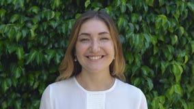 Όμορφη επιχειρηματίας που χαμογελά στο υπόβαθρο του πράσινου φράκτη των θάμνων την ηλιόλουστη ημέρα φιλμ μικρού μήκους