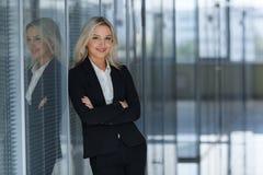 Όμορφη επιχειρηματίας που χαμογελά με τα διπλωμένα όπλα στην αρχή Στοκ Εικόνες